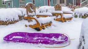 Πορφυρό έλκηθρο πανοράματος και ξύλινες καρέκλες που περιβάλλονται από το χιόνι κατά τη διάρκεια του χειμώνα στη χαραυγή στοκ εικόνα με δικαίωμα ελεύθερης χρήσης