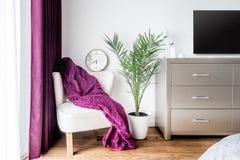 Πορφυρό κάλυμμα και ένα ρολόι τοίχων ως ντεκόρ στη σύγχρονη, μοντέρνη κρεβατοκάμαρα Στοκ Φωτογραφία