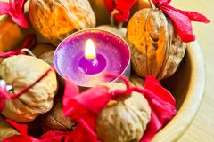 Πορφυρό κερί με διακοσμημένος wallnuts σε ένα ξύλινο κύπελλο στοκ φωτογραφίες