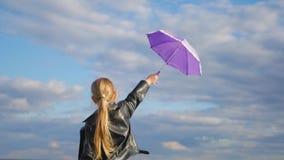 Πορφυρό μικρό κορίτσι ομπρελών ενάντια στο μπλε ουρανό φιλμ μικρού μήκους