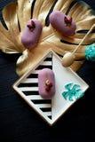 Πορφυρό mousse φρούτων κέικ, σε ένα όμορφο πιατάκι Σε ένα σκοτεινό υπόβαθρο, με ένα φύλλο του monstera που χρωματίζεται στο χρυσό Στοκ Εικόνες