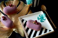 Πορφυρό mousse φρούτων κέικ, σε ένα όμορφο πιατάκι Σε ένα σκοτεινό υπόβαθρο, με ένα φύλλο του monstera που χρωματίζεται στο χρυσό Στοκ εικόνες με δικαίωμα ελεύθερης χρήσης
