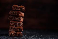 Πορώδης σοκολάτα στο σωρό σε μια μαύρη κινηματογράφηση σε πρώτο πλάνο υποβάθρου Κομμάτια της πορώδους σοκολάτας γάλακτος, που βρί Στοκ Φωτογραφίες