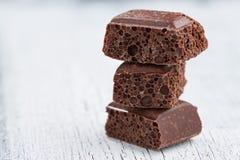 Πορώδης σκοτεινή σοκολάτα σε ένα άσπρο ξύλινο υπόβαθρο Στοκ Εικόνες