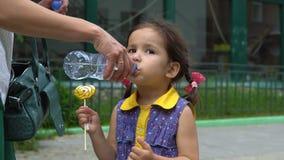Ποτά μικρά κοριτσιών από ένα πλαστικό μπουκάλι απόθεμα βίντεο