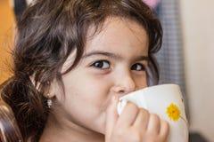 Ποτά μικρών κοριτσιών από μια κούπα του τσαγιού ή του χυμού ζητήματα δ στοκ φωτογραφίες με δικαίωμα ελεύθερης χρήσης