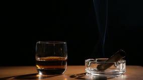 Ποτά ουίσκυ με τα καπνίζοντας πούρα απόθεμα βίντεο