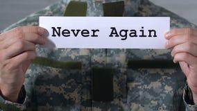 Ποτέ πάλι γραπτός σε χαρτί στα χέρια του αρσενικού στρατιώτη, έννοια παγκόσμιας ειρήνης απόθεμα βίντεο