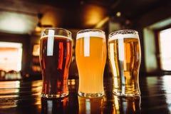 Ποτήρια της ελαφριάς και σκοτεινής μπύρας σε μια ανασκόπηση μπαρ Στοκ φωτογραφία με δικαίωμα ελεύθερης χρήσης