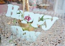 Ποτήρια της σαμπάνιας και της ευτυχούς διακόσμησης στον εορταστικό πίνακα Στοκ Φωτογραφία