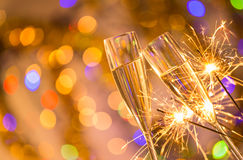 Ποτήρια της σαμπάνιας με το φωτεινό χρυσό υπόβαθρο Στοκ εικόνα με δικαίωμα ελεύθερης χρήσης