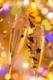 Ποτήρια της σαμπάνιας με το φωτεινό χρυσό υπόβαθρο Στοκ εικόνες με δικαίωμα ελεύθερης χρήσης