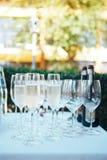 Ποτήρια της σαμπάνιας στον εορταστικό πίνακα γυαλιά σαμπάνιας υπαίθρια στοκ εικόνες