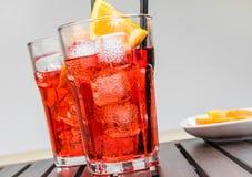 Ποτήρια του κοκτέιλ aperol απεριτίφ spritz με τις πορτοκαλιούς φέτες και τους κύβους πάγου κοντά στο πιάτο των πορτοκαλιών φετών Στοκ εικόνα με δικαίωμα ελεύθερης χρήσης