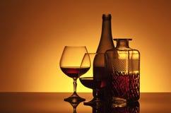 Ποτήρια του κονιάκ στο αντανακλαστικό υπόβαθρο Στοκ Φωτογραφία