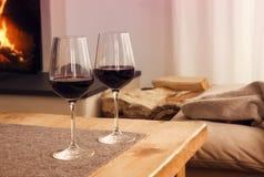 Ποτήρια του κόκκινου κρασιού μπροστά από την εστία Στοκ φωτογραφία με δικαίωμα ελεύθερης χρήσης