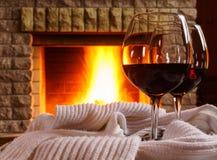 Ποτήρια του κόκκινου κρασιού πριν από την άνετη εστία Στοκ φωτογραφίες με δικαίωμα ελεύθερης χρήσης