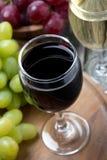 Ποτήρια του κόκκινων και άσπρων κρασιού και των σταφυλιών, τοπ άποψη Στοκ Φωτογραφία