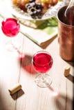 Ποτήρια του ροδαλού κρασιού στον πίνακα με τα πώματα φελλού στοκ φωτογραφία