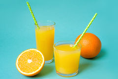 Ποτήρια του χυμού από πορτοκάλι με το άχυρο και των φετών στο φωτεινό υπόβαθρο Στοκ Φωτογραφίες