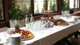 Ποτήρια των λαμπιρίζοντας κοκτέιλ και των εύγευστων πρόχειρων φαγητών σε έναν πίνακα μπουφέδων απόθεμα βίντεο