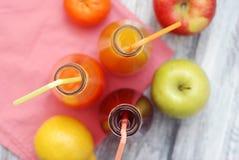 Ποτήρια χυμού πρόσφατα του χυμού φρούτων με τα ζωηρόχρωμα φρούτα στο αγροτικό γκρίζο ξύλινο υπόβαθρο τρόφιμα έννοιας υγιή στοκ φωτογραφίες με δικαίωμα ελεύθερης χρήσης