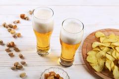 Ποτήρι δύο της μπύρας και των πρόχειρων φαγητών σε έναν άσπρο ξύλινο πίνακα Τσιπ, φυστίκια, ξηρό τυρί στοκ φωτογραφίες