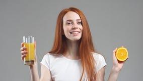 Ποτήρι εκμετάλλευσης κοριτσιών του χυμού από πορτοκάλι και του γέλιου στη κάμερα απόθεμα βίντεο