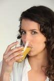 Ποτήρι κατανάλωσης Brunette του χυμού Στοκ φωτογραφία με δικαίωμα ελεύθερης χρήσης