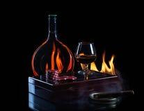 Ποτήρι μπουκαλιών του κονιάκ με τους δείκτες και το πούρο πόκερ Στοκ Εικόνες