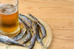 Ποτήρι της μπύρας και των αποξηραμένων ψαριών σε ένα μαγειρεύοντας φύλλο, παραδοσιακό πρόχειρο φαγητό μπύρας Στοκ Εικόνες
