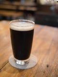 Ποτήρι της μπύρας στον ξύλινο πίνακα στοκ εικόνα