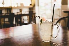 Ποτήρι της παγωμένης λεμονάδας με τη φέτα λεμονιών στον καφετή ξύλινο πίνακα Στοκ φωτογραφίες με δικαίωμα ελεύθερης χρήσης