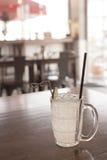 Ποτήρι της παγωμένης λεμονάδας με τη φέτα λεμονιών στον καφετή ξύλινο πίνακα Στοκ Φωτογραφία