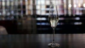 Ποτήρι της σαμπάνιας στο φραγμό σε ένα λαμπυρίζοντας υπόβαθρο φιλμ μικρού μήκους