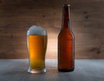 Ποτήρι της χρυσών μπύρας και του μπουκαλιού Στοκ εικόνα με δικαίωμα ελεύθερης χρήσης