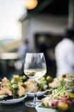 Ποτήρι του άσπρου κρασιού με τα γαστρονομικά πρόχειρα φαγητά tapa τροφίμων έξω Στοκ εικόνες με δικαίωμα ελεύθερης χρήσης