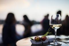 Ποτήρι του άσπρου κρασιού με τα γαστρονομικά πρόχειρα φαγητά tapa τροφίμων έξω Στοκ φωτογραφία με δικαίωμα ελεύθερης χρήσης