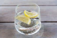 Ποτήρι του λαμπιρίζοντας νερού με το λεμόνι στον πίνακα Στοκ Εικόνες