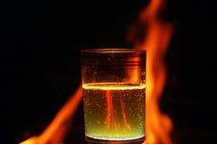 Ποτήρι του αφρώδους νερού μπροστά από την πυρκαγιά στοκ εικόνες με δικαίωμα ελεύθερης χρήσης