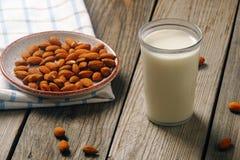 Ποτήρι του γάλακτος αμυγδάλων με τα καρύδια αμυγδάλων στον αγροτικό ξύλινο πίνακα Εναλλακτικά τρόφιμα Vegan, μη γαλακτοκομικό γάλ στοκ φωτογραφίες με δικαίωμα ελεύθερης χρήσης