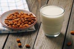 Ποτήρι του γάλακτος αμυγδάλων με τα καρύδια αμυγδάλων στον αγροτικό ξύλινο πίνακα Εναλλακτικά τρόφιμα Vegan, μη γαλακτοκομικό γάλ στοκ φωτογραφίες