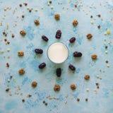 Ποτήρι του γάλακτος σε ένα μπλε υπόβαθρο με διεσπαρμένο το ημερομηνίες muesli Στοκ φωτογραφία με δικαίωμα ελεύθερης χρήσης