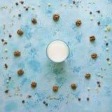 Ποτήρι του γάλακτος σε ένα μπλε υπόβαθρο με διεσπαρμένο το ημερομηνίες muesli Στοκ εικόνα με δικαίωμα ελεύθερης χρήσης
