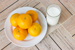 Ποτήρι του γάλακτος και του πορτοκαλιού στα ξύλινα υπόβαθρα Στοκ εικόνες με δικαίωμα ελεύθερης χρήσης
