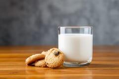 Ποτήρι του γάλακτος και των μπισκότων στον ξύλινο πίνακα Στοκ Εικόνες