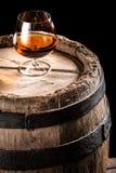 Ποτήρι του ηλικίας κονιάκ και του παλαιού ξύλινου βαρελιού στοκ εικόνα με δικαίωμα ελεύθερης χρήσης