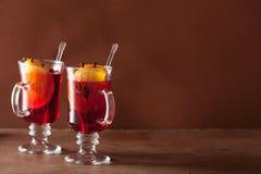 Ποτήρι του θερμαμένου κρασιού με το πορτοκάλι και τα καρυκεύματα, χειμερινό υπόβαθρο Στοκ Εικόνες