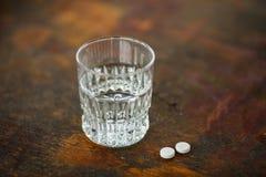 Ποτήρι του καθαρού νερού και λίγων χαπιών Στοκ φωτογραφία με δικαίωμα ελεύθερης χρήσης
