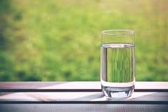 Ποτήρι του καθαρού νερού στο πράσινο φυσικό υπόβαθρο στοκ εικόνες